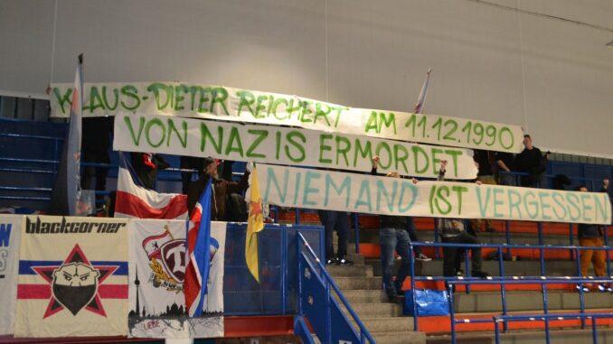 """Gedenktapete im Fanblock während eines Eishockeyspiels. Darauf steht """"Klaus-Dieter Reichert, am 11.12.1990 von Nazis ermordet. Niemand ist vergessen"""""""